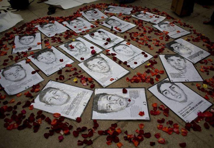 Esta foto de archivo de 2015 muestra bocetos rodeados de pétalos de algunos de los 43 estudiantes desaparecidos en septiembre de 2014. La CNDH de México presentó un documento de denuncia por fallos y omisiones en la investigación. (AP Photo/Rebecca Blackwell, File)