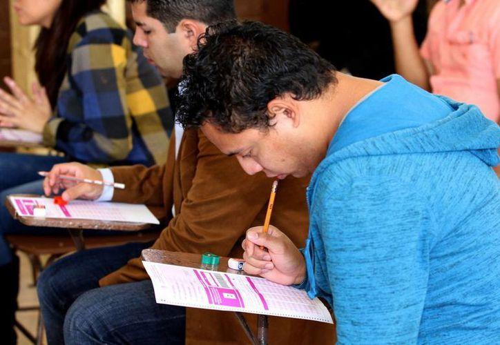 Los profesores mexicanos no sólo gastan la mitad de su tiempo en no hacer nada, sino que tiene mal manejo de los contenidos. Imagen de contexto de profesores que presentan un examen para obtener una plaza. (Archivo/NTX)