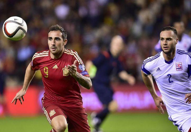 España goleó a Luxemburgo y clasificó este viernes a la Eurocopa Francia 2016, donde buscará convertirse en el primer tricampeón continental consecutivo. En la foto, el ibérico Paco Alcántara (i) lucha por la pelota con Massimo Martino. (AP)