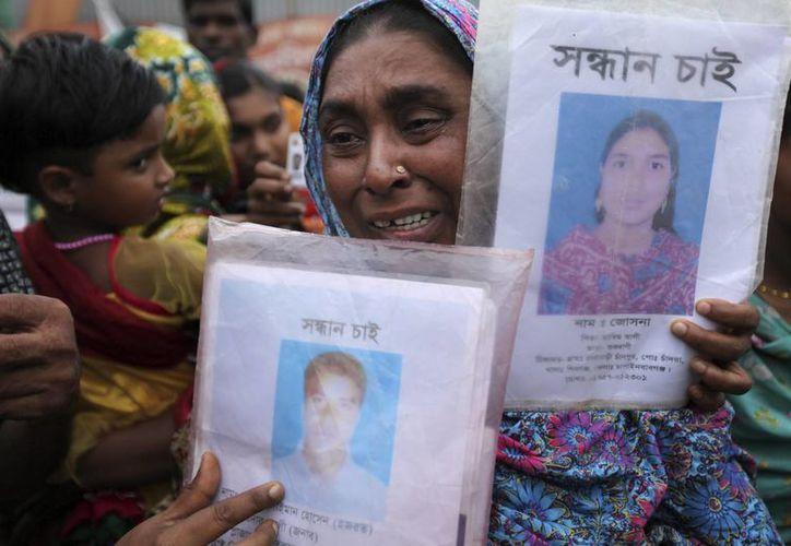 Una mujer sostiene las fotografías de sus seres queridos fallecidos en el derrumbe del edificio de talleres textiles Rana Plaza en Savar, Bangladesh, durante una concentración en la que han exigido compensaciones y rehabilitación para los afectados seis meses después del derrumbe. (EFE/Archivo)