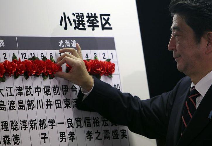 El líder de la oposición japonesa Shinzo Abe, del Partido Demócrata Liberal, marca el nombre de uno de los elegidos en las elecciones parlamentarias, en Tokio. (Agencias)