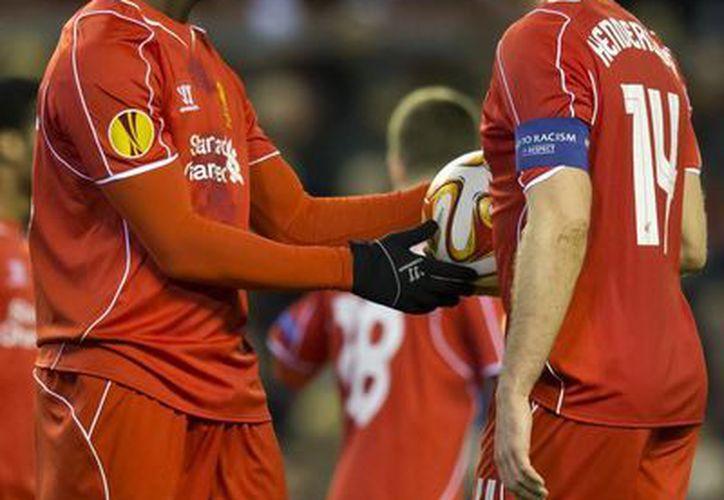 Mario Balotelli (i) volvió a protagonizar una acción polémica al casi arrebatarle el balón al capitán del Liverpool, Jordan Henderson, para cobrar un penal ante Besiktas. (Foto:Ap)