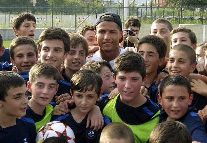 Cristiano departió un buen rato con los chavales y les firmó autógrafos, pero no hizo alardes con el balón. (EFE)