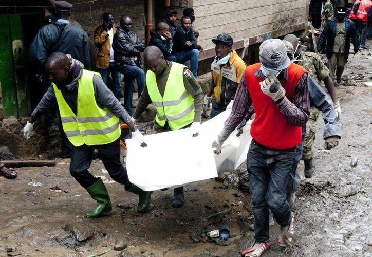 Voluntarios transportan el sábado 30 de abril de 2016 un cadáver recuperado de entre los escombros de un edificio que se derrumbó la noche anterior en Nairobi, Kenya. (Agencias)
