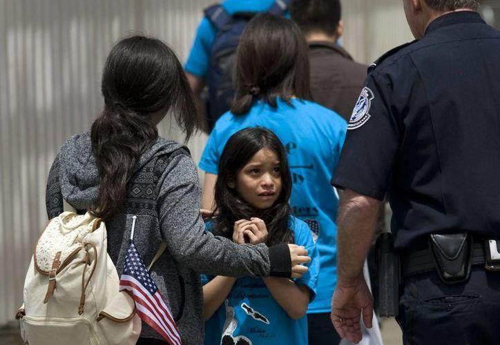 Una niña observa a un oficial estadounidense de fronteras, mientras ingresa a Estados Unidos con su familia por la garita de San Ysidro en la frontera entre Estados Unidos y Tijuana, México. (EFE/Archivo)