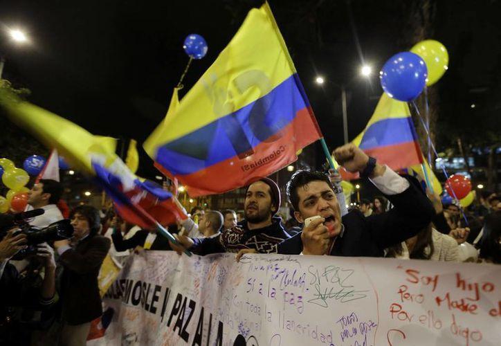El anuncio de la paz entre las FARC y el gobierno despertó el júbilo de los colombianos, quienes no tardaron en salir a las calles de Bogotá a festejar. (AP)