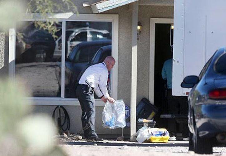 Investigadores del Departamento de Policía de Tucson inspeccionan la casa donde las tres víctimas fueron retenidas durante dos años. (Agencias)
