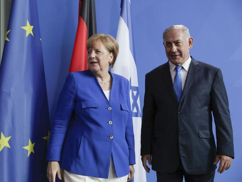 German Chancellor Angela Merkel, left, and Israel's Prime Minister Benjamin Netanyahu, right, shake hands after a joint press conference in Berlin, Germany.