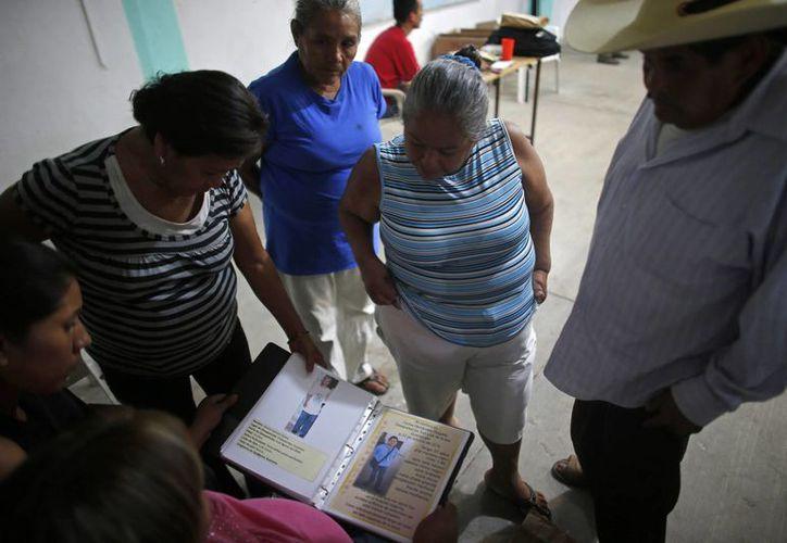 Familiares de personas desaparecidas repasan un archivo lleno de imágenes e información sobre personas desaparecidas, en un sótano de la iglesia de San Gerardo, en Iguala, Guerrero. (Agencias)
