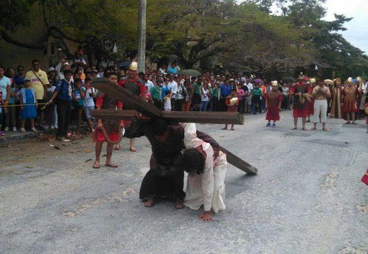 Simón de Cirene le ayuda a cargar la cruz a 'Cristo', en las calles de Cancún. (Carlos Ávalos/SIPSE)