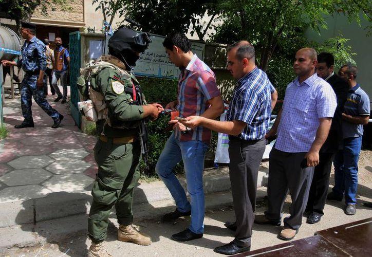 Las fuerzas de seguridad iraquíes hacen cola para votar fuera de un centro de votación en Bagdad, Irak. (Agencias)