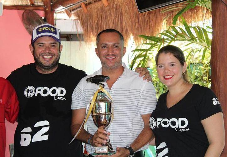 Hugo Bonilla, con su trofeo de campeón, fue felicitado por Alejandro Arcos y Ninfa Gabbi. (Raúl Caballero/SIPSE)