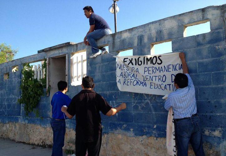 Los profesores colocaron mantas en las escuelas. (Adrián Barreto/SIPSE)
