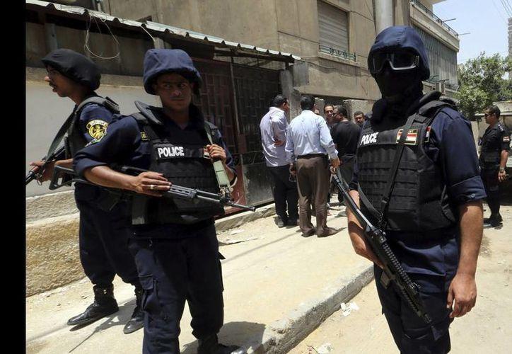 Quedó deshecho el coche en el que viajaban los presuntos terroristas, que aún no han sido identificados. En la foto de archivo, policías de Egipto. (EFE)