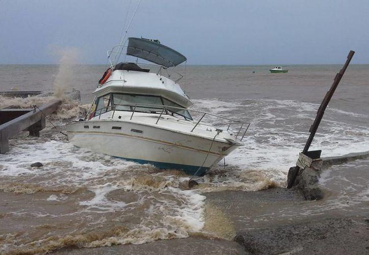 Un yate es remecido por el oleaje en Dominica, en el Caribe Oriental, donde la tormenta Erika dejó como saldo cuatro muertos. Ahora Erika avanza sobre Puerto Rico este viernes 28 de agosto de 2015. (Foto: AP)