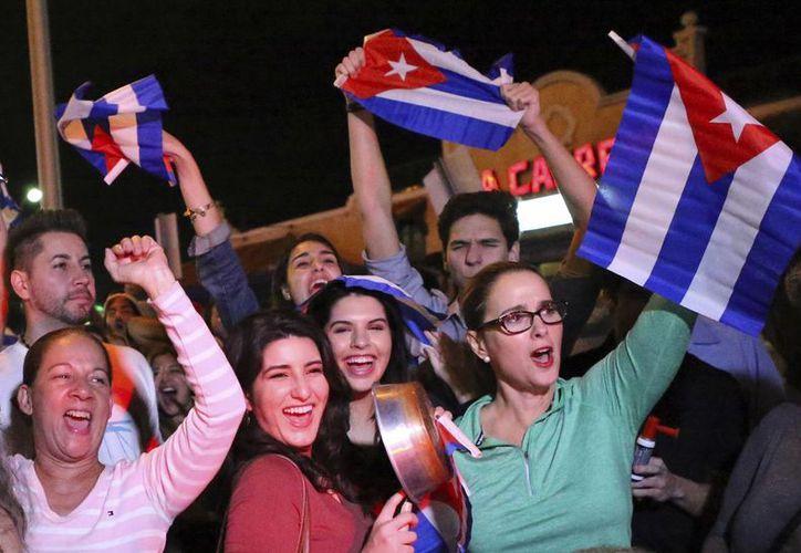 Miembros de la comunidad cubana de Miami celebran la noticia de la muerte de Fidel Castro delante del restaurante La Carreta en Miami. (AP/David Santiago)