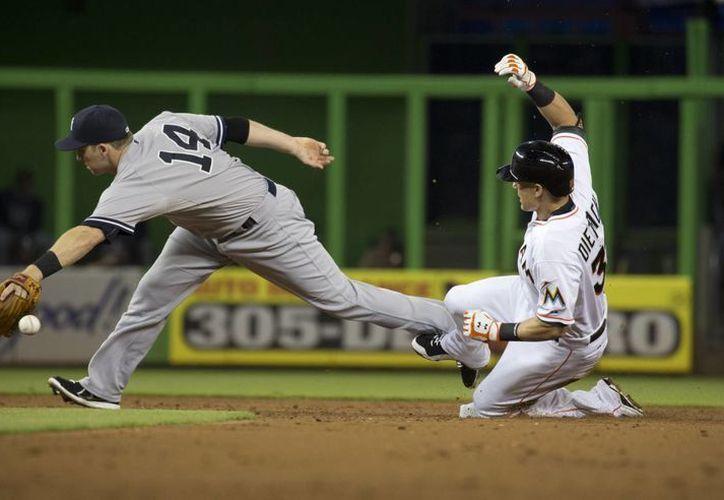 El segunda base de Yanquis, Stephen Drew (14), atrapa la pelota mientras Derek Dietrich (32), de Marlins, se desliza hacia la segunda base en partido ganado por Marlins. (Foto: AP)