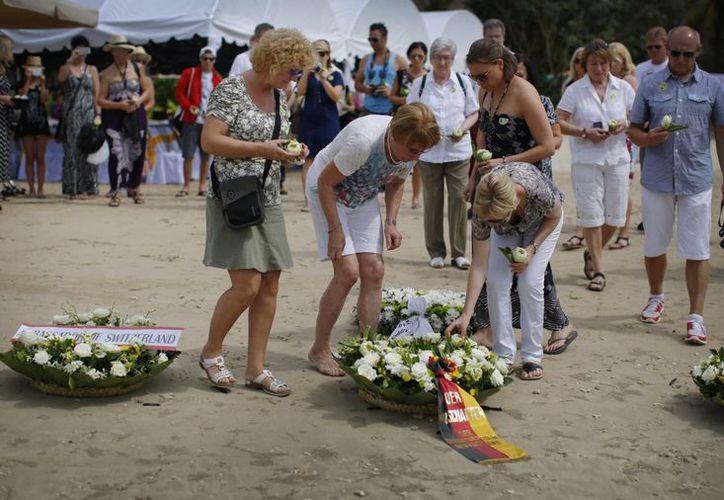 Familiares de víctimas del tsunami en Asia colocan flores durante la ceremonia con que se recordó el décimo aniversario de este fenómeno, en Khao Lak, Tailandia. (Foto: AP)