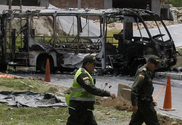 """Autoridadaes acuden al lugar en donde un autobusbus del sistema de transporte público fue incinerado en Medellín por grupos que apoyan el """"paro armado"""" generado por el Clan Úsuga. (EFE)"""
