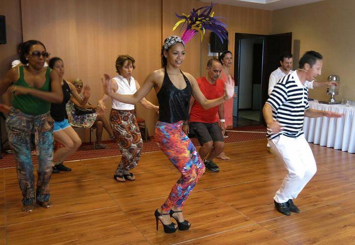 Nete Vieira, centro, y su esposo Naldi, derecha, enseñan samba a extranjeros en Río de Janeiro, Brasil. (Agencias)