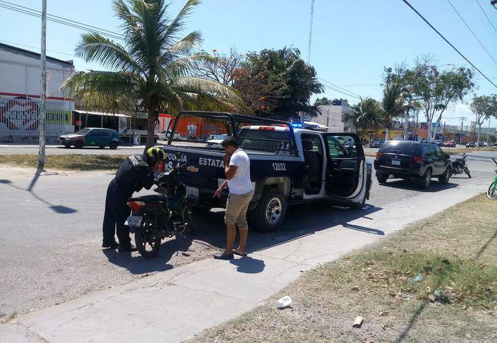 Un elemento de la Policía Estatal derrapó en su moto por unos perros, pero saltó y resultó ileso. (Foto: Redacción/SIPSE)
