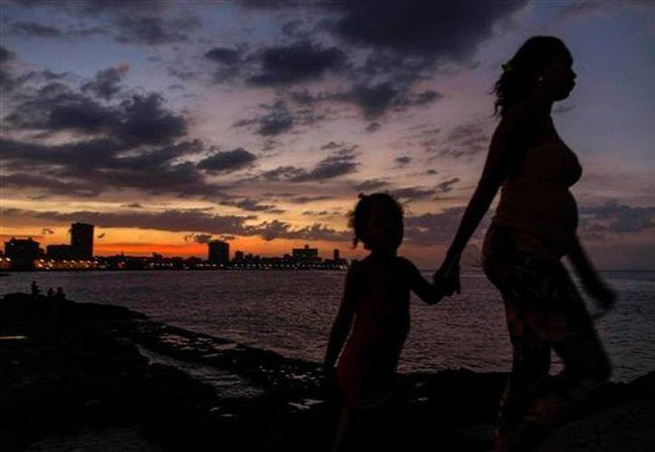 Una mujer lleva a una niña de la mano en el malecón de La Habana, Cuba. (Agencias)