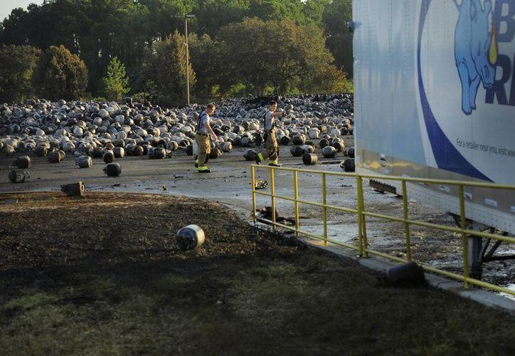 Bomberos caminan entre bombonas de butano que permanecen esparcidas por el suelo en los alrededores de la compañía de gas Blue Rhino en Tavares, Florida. (EFE)