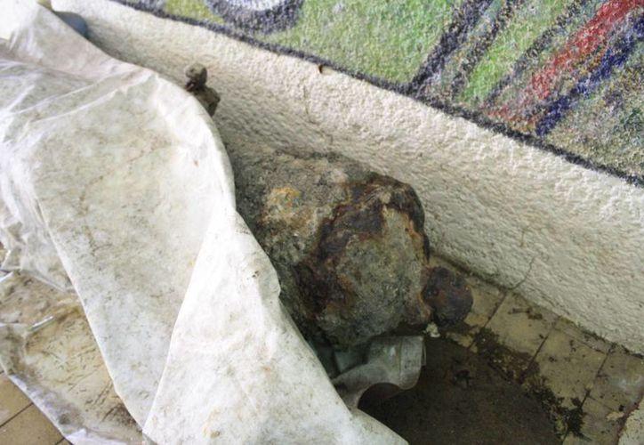 La pieza arqueológica se encuentra cubierta con una lona. (Harold Alcocer/SIPSE)