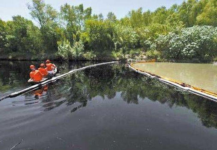 Trabajadores de Pemex se encuentran en el río San Juan para recuperar las toneladas de hidrocarburo derramados. (Daniel Becerril/Reuters)