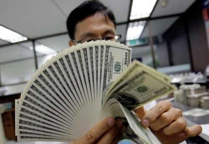 Centros cambiarios de Mérida ofertaron el billete verde en un precio máximo de 12.85 pesos. (Archivo)