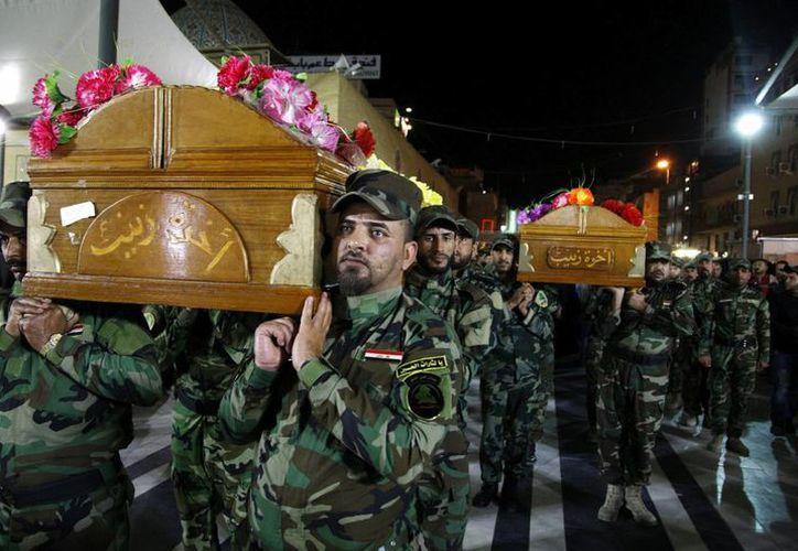 Miembros del grupo chií iraquí Kataib Hizbulá trasladan el ataúd con los restos mortales de uno de sus compañeros, que murió durante enfrentamientos con yihadistas del Estado Islámico. (EFE)