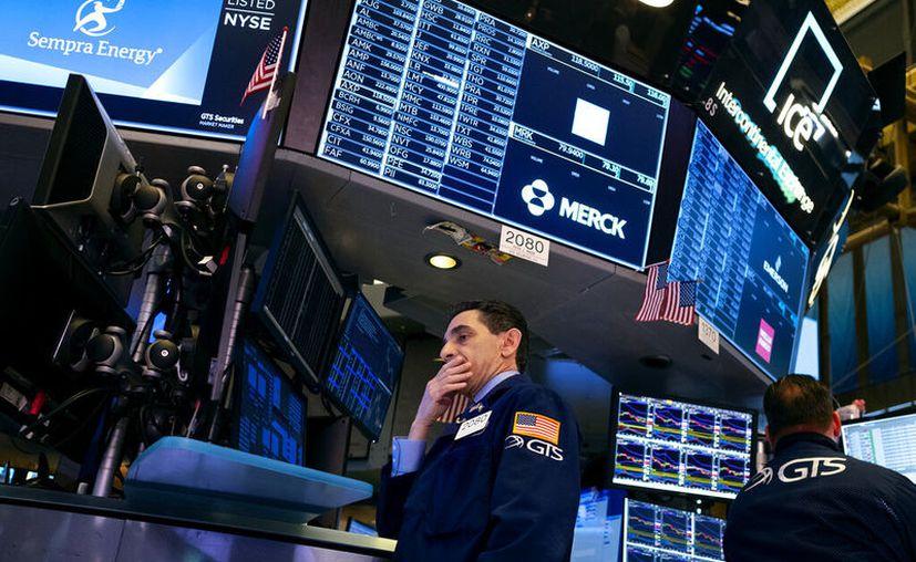 El corredor bursátil Peter Mazza examina acciones en la Bolsa de Valores de Nueva York. (AP Foto/Craig Ruttle)