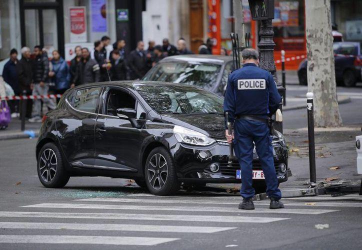 Gendarmes de la Policía junto a un coche sospechoso en el bulevard Ornanon durante la investigación de los atentados en París, Francia. (EFE)