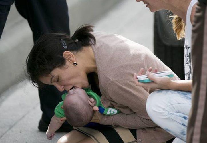 Pamela Rauseo practica respiración artificial en su sobrino Sebastián de la Cruz, de cinco meses, después de detener su vehículo en una carretera de Florida, a la derecha Lucila Godoy, que también detuvo su auto para ayudar. (Agencias)