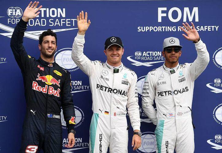 Nico Rosberg(c) obtuvo su segunda 'pole' consecutiva, venciendo a Lewis Hamilton (d). En la foto, los tres primeros lugares de la clasificación del Gran Premio de Alemania.(AP)