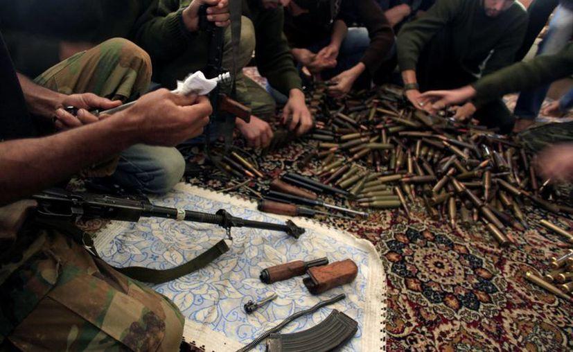Combatientes del Ejército sirio limpian sus armas y municiones en su base en las afueras de Alepo, Siria. (Agencias)