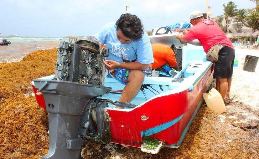 Los dueños de embarcaciones menores han tenido que realizar arreglos en sus motores afectados por el sargazo. (Daniel Pacheco/SIPSE)