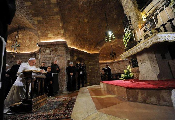 El papa Francisco (i) reza ante la tumba de San Francisco de Asís en Asís, Italia. (EFE)