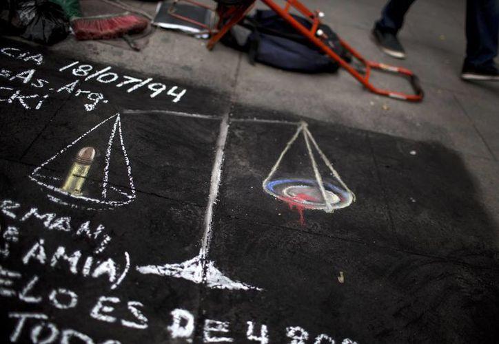 Un dibujo con la balanza de la justicia, con una bala en un lado y sangre en el otro, fue pintado en una acera de Buenos Aires, Argentina. (Agencias)