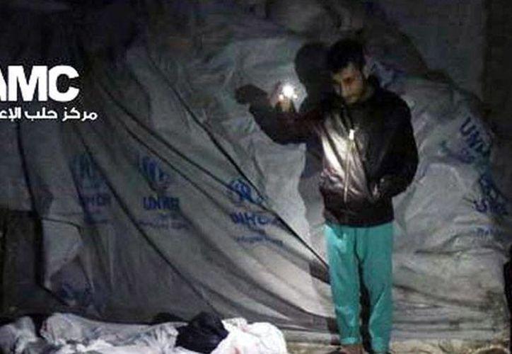 Imagen difundida por Alepo Media Center en la que puede verse a un hombre que observa los cuerpos de las víctimas de los ataques de Fuerzas del Gobierno, en Alepo. (AP)