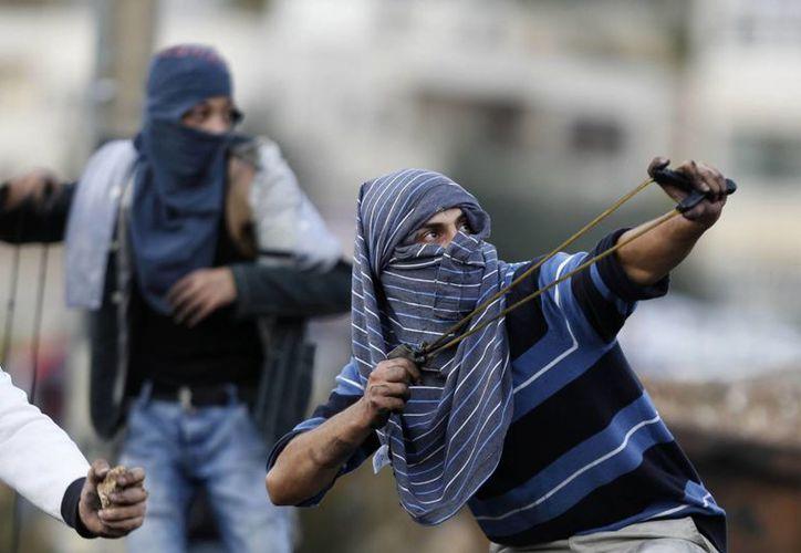 Palestinos usan hondas para lanzar piedras durante los enfrentamientos con las tropas israelíes. (Agencias)