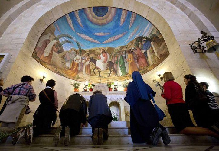 Fieles católicos se arrodillan ante un mural de Jesús en un santuario de Jerusalén Este. (EFE)