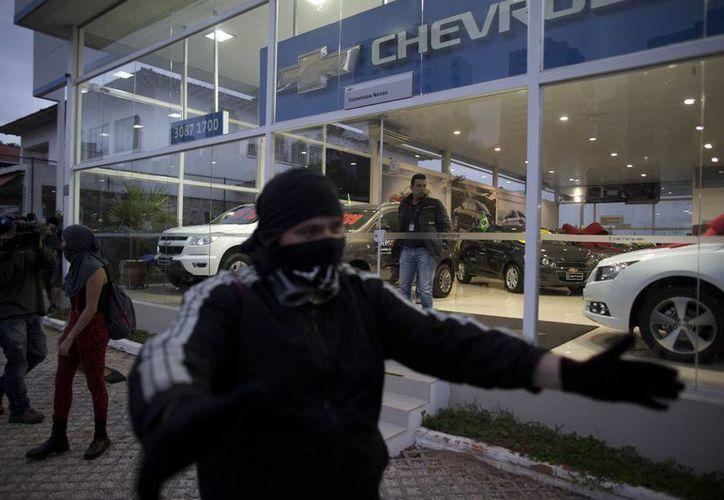 Algunas personas vestidas de negro atacaron un vehículo de una emisora de televisión y la fachada de un banco. (Foto: AP)