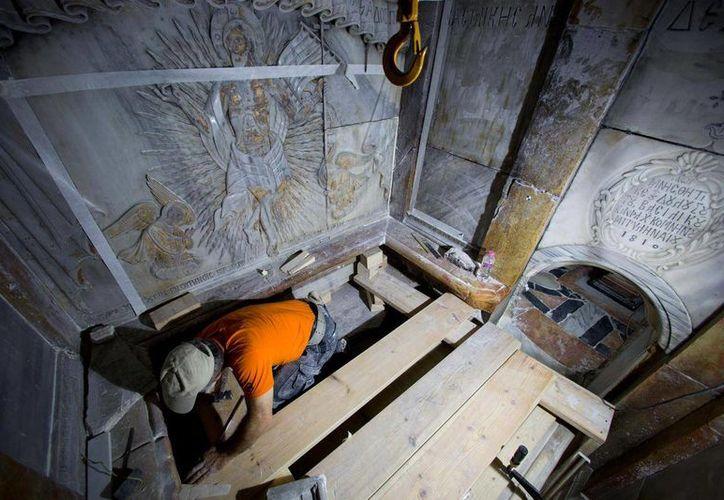 Un conservador limpia la superficie de la losa de piedra venerada como el lugar de descanso final de Jesucristo. (Oded Balilty/AP/para National Geografic)