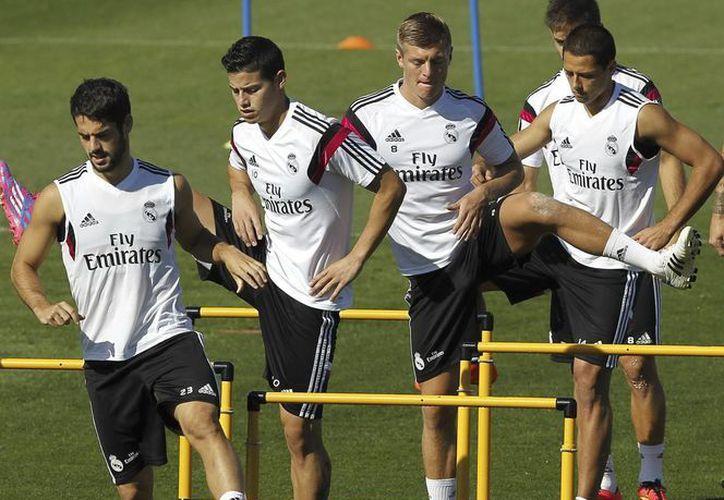 Los jugadores del Real Madrid: Isco (i), James Rodriguez (2i), Kross (2d) y 'Chicharito' (d) entrenan junto con sus compañeros antes del derbi madrileño de este fin desemana ante el Atlético de Madrid. (EFE)