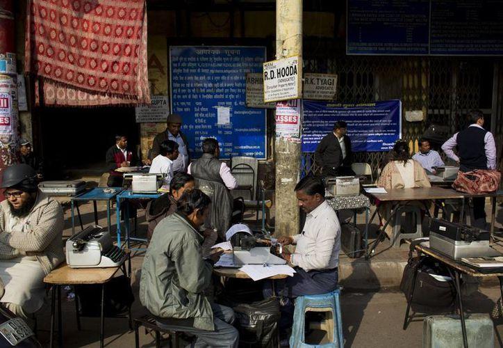 Mecanógrafos profesionales ofrecen sus servicios en la calle, cerca de bolsa de valores de Nueva Delhi. (AP/Bernat Armangue)