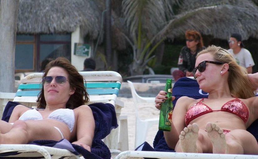 Varias visitantes aprovecharon el fuerte sol que hizo ayer en Progreso para broncear sus cuerpos. (Manuel Pool/SIPSE)