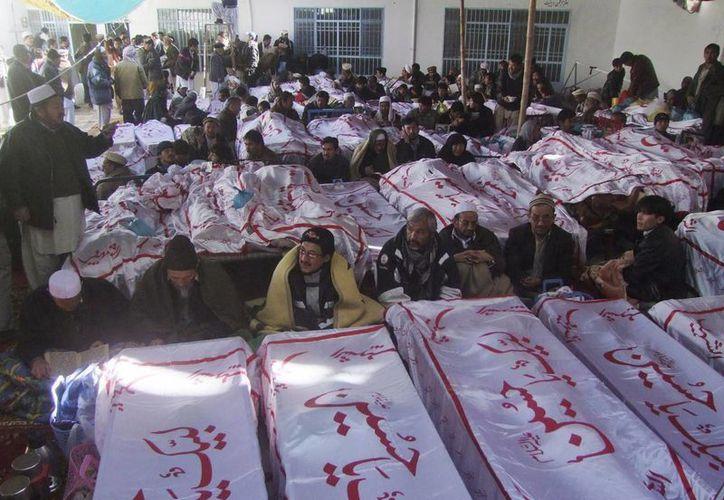 Musulmanes chiíes se sientan junto a las victimas del atentado perpetrado el pasado sábado, a las que se niegan enterrar hasta que el Gobierno acepte sus peticiones. (EFE)