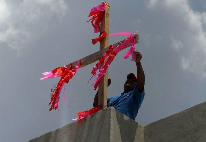 El 3 de mayo de cada año, los trabajadores de la construcción acostumbran colocar una cruz de madera adornada con flores y papel de china en lo alto de la obra en construcción. (Archivo/SIPSE)