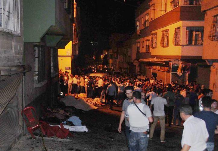 Imágenes captadas tras un estallido durante una boda en Turquía mostraron varios cuerpos cubiertos con sábanas blancas mientras una multitud se reunía a su alrededor. (Eyyup Burun/DHA via AP)